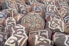 Pebbles from sacred Lake Manasarovar with hieroglyphs and main Buddhist mantra `Om Mani Padme Hum`. Royalty Free Stock Images