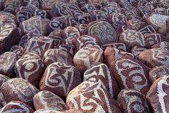 Pebbles from sacred Lake Manasarovar with hieroglyphs and main Buddhist mantra `Om Mani Padme Hum`. Stock Photography