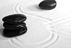 Pebbles on sand. Shiny black pebbles on white sand Stock Photography