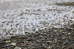 Pebbles on a sandy beach, shiny wet stones and waves.  stock photos
