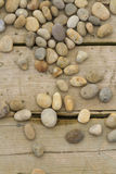 Pebbles  scattered on wood. Pebbles scattered over wooden planks Stock Photos