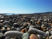 Pebbles on the sea beach close-up with blurred background of the sea. Summer. Pebbles on the sea beach close-up with blurred background of the sea. Pebble beach royalty free stock images