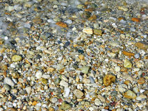 Pebbles and sea foam on the beach – background Royalty Free Stock Images