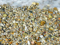 Pebbles and sea foam on the beach – background Royalty Free Stock Photography