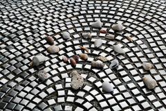 Pebbles and seashells  on the tile, paving. Stones, shells and urban life style. Pebbles and seashells  on the tile, paving. Stones, shells and urban life Royalty Free Stock Image