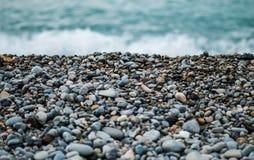 Pebbles on Seashore by Ocean Stock Photography