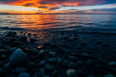 Pebbles on the shore of Lake Baikal against the backdrop of the sunset Stock Image