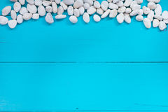 Pebbles on the side over a textured painted blue background Stock Photo