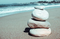 Pebbles stack balance on the beach. Pebbles stack balance over blue sea in Antalia Turkey. Blue sky and water on sunny coast in summer. Zen meditation background Royalty Free Stock Image