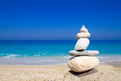 Pebbles stack balance over blue ionian sea. In Greece. Blue sky and water on sunny coast in summer Stock Photo