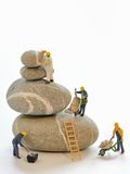 Pebbles stack and figurines of construction workers Stock Photo