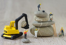 Pebbles stack and figurines workers Stock Images