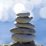 Pebbles stack over blue sea. With reflections Stock Photos