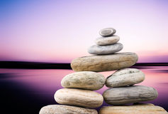 Pebbles stack in peaceful evening. With smooth ocean background. Zen concept stock photography