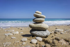 Pebbles stacked up on a cove. Some pebbles stacked up on a cove in Spain with a beautiful blue sky and clean water in the background Royalty Free Stock Photo