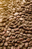 Pebbles stone wall background kissed by the sun. Close view Royalty Free Stock Images