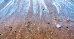 Pebbles or stones or rocks on beach at low tide. Seascape, nature, zen, tranquility concept wallpaper or background with copy. Space stock images