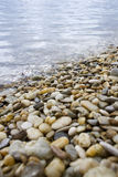 Pebbles and stones at a shore Stock Photos