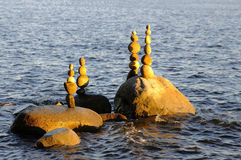 Pebbles and stones stacked on a rock seashore Royalty Free Stock Photos