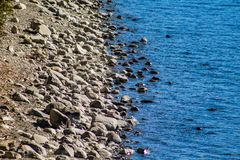 Pebbles and stones at waterfront, Lake Coleridge, South Island, New Zealand stock photography
