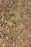 Pebbles texture with on half covered by sea water stock images