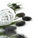 Pebbles, towel and palm leaf Stock Photos