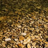 Pebbles under water. Sunlight, quick river and ripples Royalty Free Stock Images