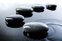 Pebbles in Water. A row of shiny black pebbles in water Royalty Free Stock Image