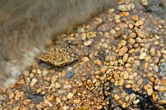 Pebbles and waves in the freshwater reservoir. Freshwater wave is hitting the coastal line of the seashore Stock Photo