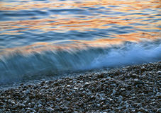 Pebbles and the waves at sunset. Blurred waves and pebbles at Adriatic blue orange sea (Croatia - Dalmatia) in sunset . Photographed using a long exposure royalty free stock image