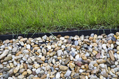 Pebblestones und grünes Gras Stockfotografie