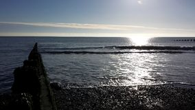 Pebbly beach reflecting the sun. The sun reflecting in an English beach`s sea in December Stock Photography