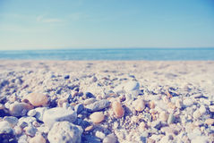Pebbly beach on a sunny summer day, low angle view; faded, retro style Stock Image