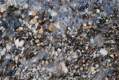Pebbly beach through the wave surging Royalty Free Stock Photos