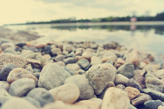 Pebbly lake shore on a summer afternoon, retro style Stock Photos