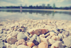 Pebbly lake shore on a sunny summer afternoon, vintage Royalty Free Stock Photo