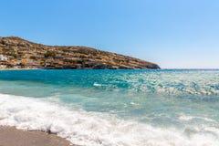 Pebbly strand Matala, Grekland Kreta Matala har blivit berömd för konstgjorda neolitiska grottor, snidit i kalksten vaggar Arkivbild