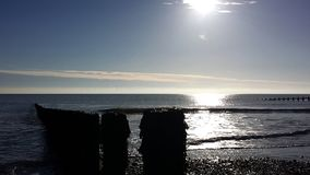 Pebbly strand som reflekterar solen royaltyfri bild