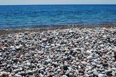 Pebles on beach. Mediterranean Sea and beach full of stones Stock Photos