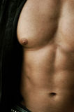 Pec and abs. Muscular male body closeup wearing an open shirt Royalty Free Stock Photo