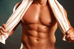 Pec and abs with towel. Muscular male body closeup of torso with a white towel slung around his neck Stock Photos