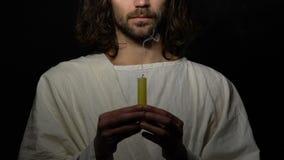 Pecador masculino en el traje que sopla emocionalmente la vela en el fondo oscuro, rechazando a dios almacen de video