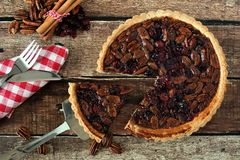 Pecan and cranberry pie, rustic table scene with slice removed. Pecan and cranberry autumn pie, overhead table scene on rustic wood with slice being removed royalty free stock photos