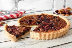 Pecan cranberry pie with slice removed on white wood Royalty Free Stock Image