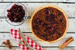 Pecan and cranberry pie table scene on rustic white wood Stock Photos