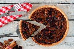 Pecan cranberry pie table scene with slice being removed Stock Photo