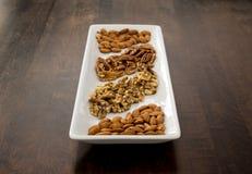 Pecan, noci e mandorle sistemati sul vassoio bianco, prospettiva fotografie stock