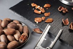 Pecan nuts with nutcracker. On gray background Royalty Free Stock Photos