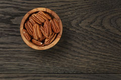 Pecan nuts in olive wood bowl on oak table Stock Images