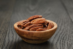 Pecan nuts in olive wood bowl on oak table Stock Photography